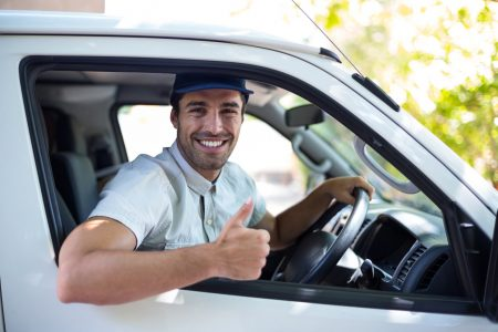 Portrait of cheerful delivery man showing thumbs up while driving van