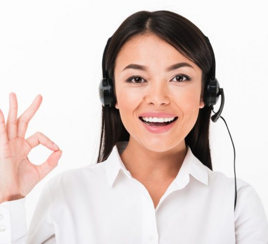 Close up of a cheerful asian woman in white shirt wearing headset with microphone showing ok gesture isolated over white background