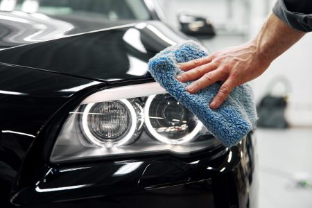 Car detailing - the man holds the microfiber in hand and polishes the car.
